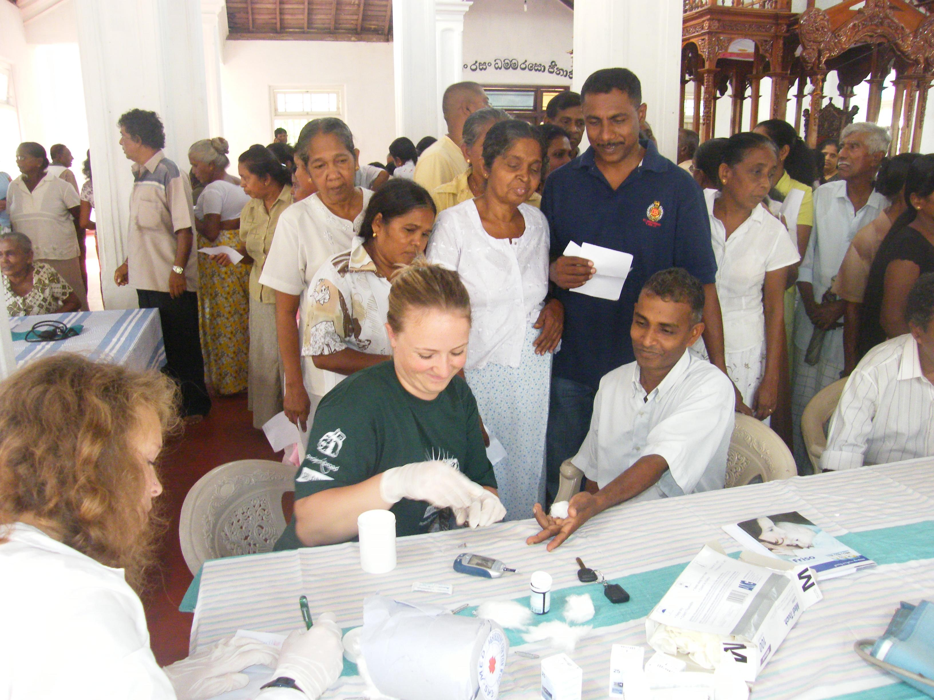 Two female interns on a nursing internship in Sri Lanka are seen helping at a medical camp assisting patients.